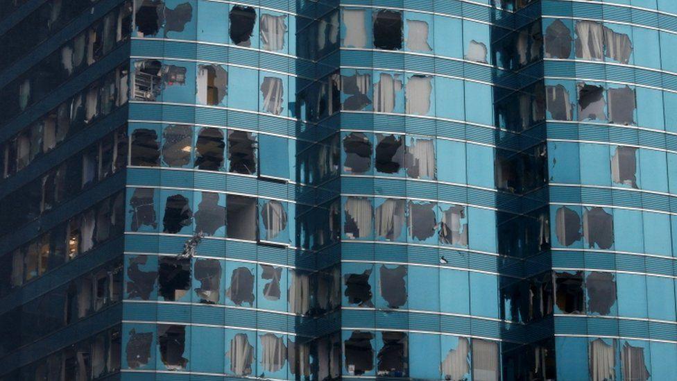 A high-rise Hong Kong building has dozens of smashed windows