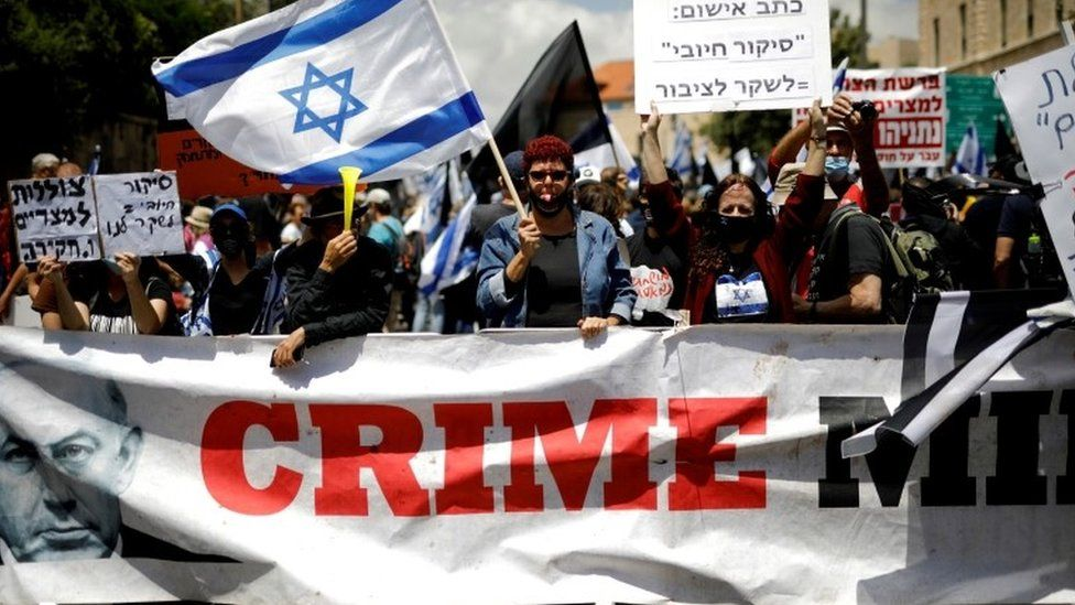 """Protesters wave an Israeli flag and hold placards as they stand behind a banner reading """"Crime Minister"""" before the start of Benjamin Netanyahu's corruption trial in Jerusalem (24 May 2020)"""