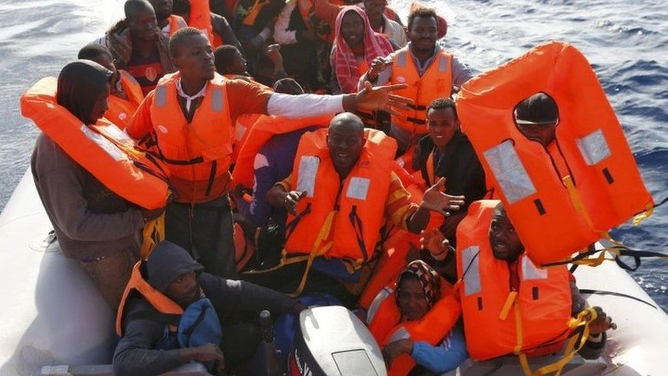 Migrants in a dinghy reach out for life jackets thrown to them by rescuers of the Migrant Offshore Aid Station (MOAS) some 20 nautical miles off the coast of Libya, June 23, 2016
