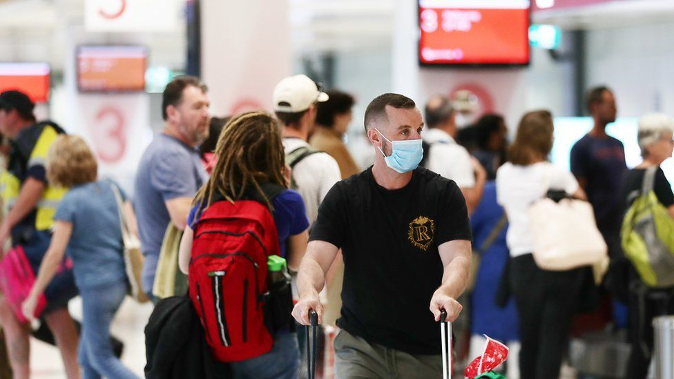 Traveller arriving from Melbourne wears a mask as he wheels baggage through crowd at Sydney domestic airport on 2 July 2020