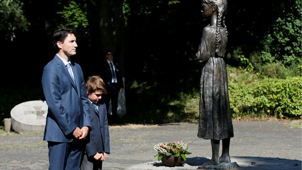 Justin Trudeau and his son Xavier place flowers at a monument for Holodomor victims in Kiev, Ukraine, July 11, 2016
