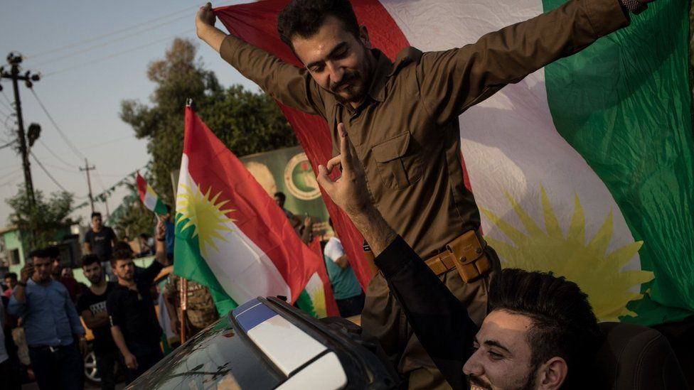 People celebrate on the streets after voting on September 25, 2017 in Kirkuk,