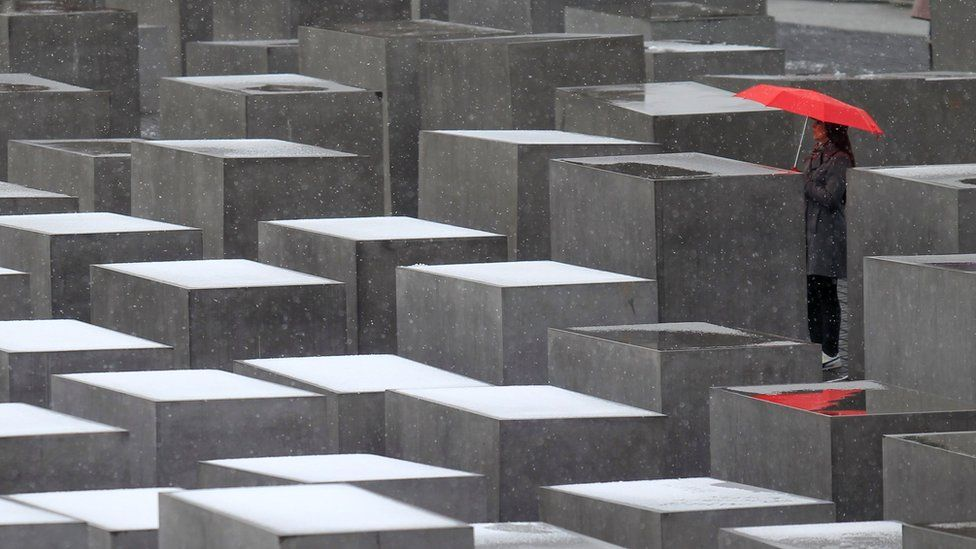 Woman stands with red umbrella at Berlin Holocaust memorial