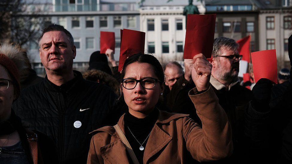 Hundreds of protesters gather in front of the parliament building holding red cards for a fourth day on 7 April 2016 in Reykjavik, Iceland after Prime Minister Sigmundur David Gunnlaugsson stepped down on revelations in the Panama Papers that he hid his assets in an offshore shell-company