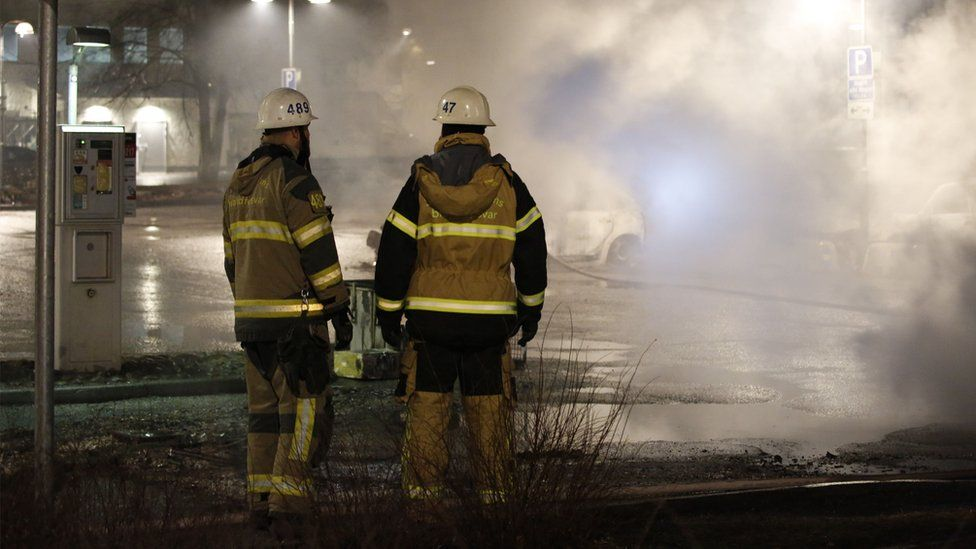 Fire fighters look at smoke in the suburb Rinkeby, outside Stockholm, on 20 February 2017