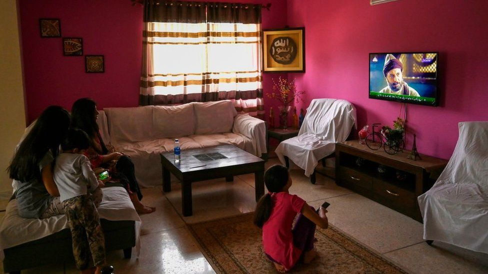 """In this picture taken on May 9, 2020, a family watches a Turkish drama series """"Dirilis: Ertugrul"""" telecasted on Pakistan's state-run channel PTV Home during the holy month of Ramadan in Islamabad"""
