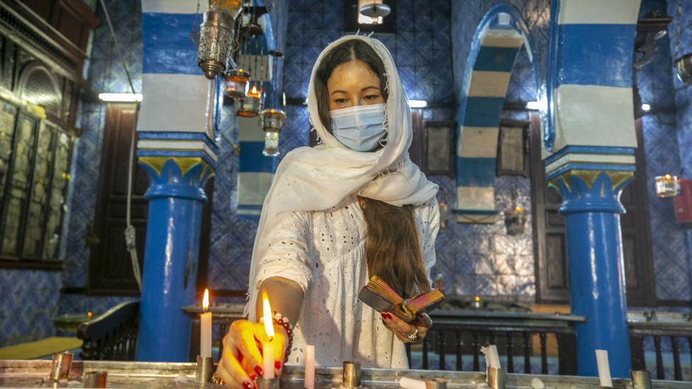 A woman lights a candles at Ghriba Synagogue, Djerba, Tunisia - Friday 30 April 2021