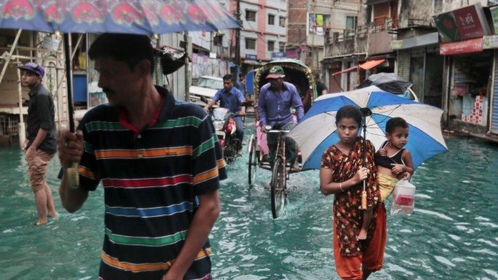 Bangladeshi people walk through waterlogged streets in Bangladesh