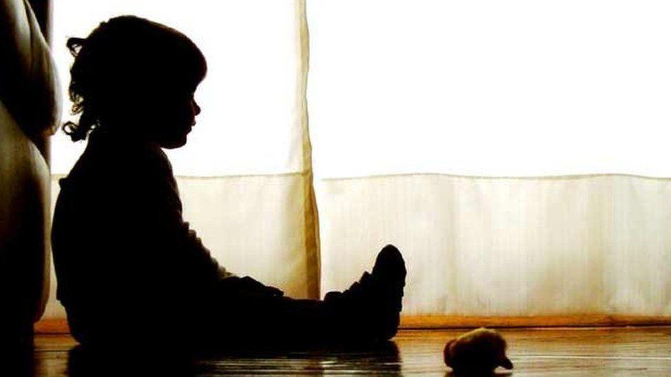 A little girl sat alone in the dark.