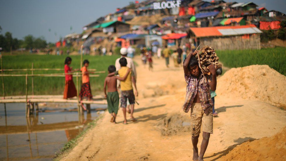 A young Rohingya boy carries a bundle of wood on his shoulder down the earthen path of Palong Khali refugee camp, Bangladesh