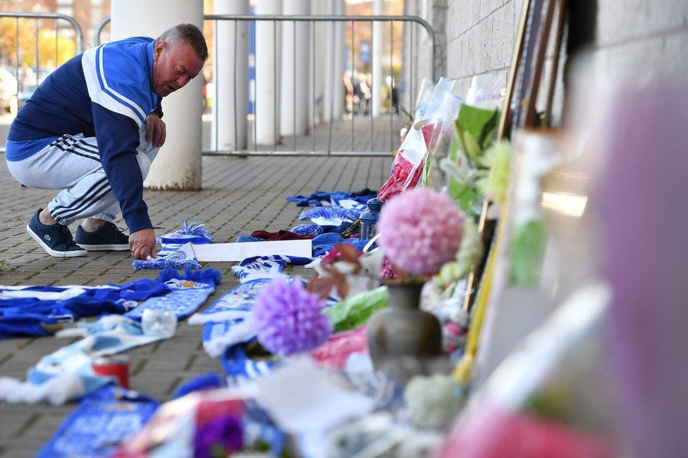 A man adds a Leicester City scarf to floral tributes lined up outside Leicester City Football Club's King Power Stadium in Leicester, eastern England, on October 28, 2018 after a helicopter belonging to the club's Thai chairman Vichai Srivaddhanaprabha crashed outside the stadium the night before
