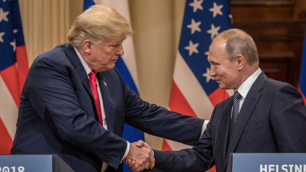 U.S. President Donald Trump (L) and Russian President Vladimir Putin shake hands during a joint press conference after their summit