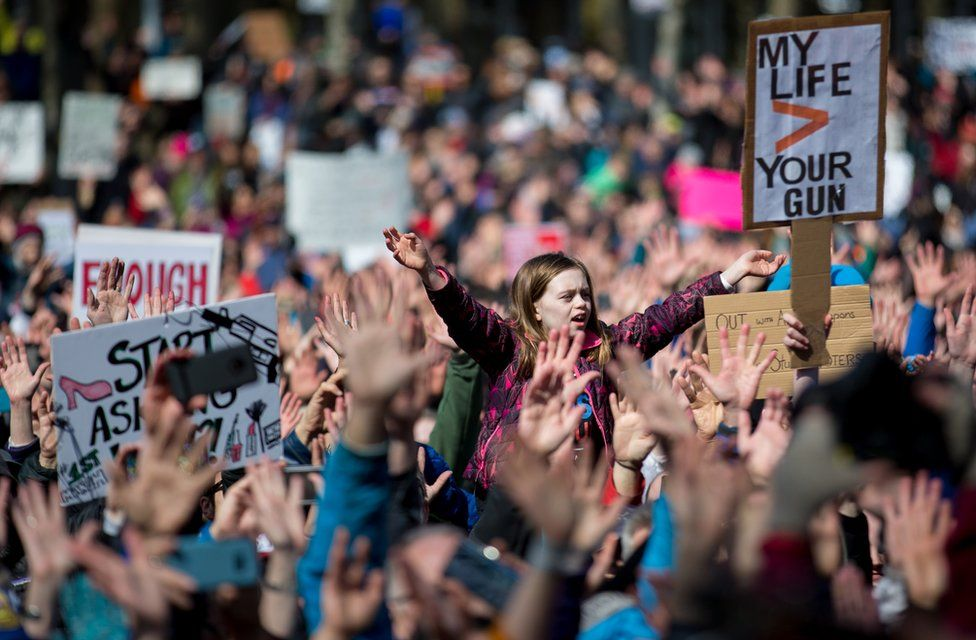 A young girl raises her hands with hundreds of others during the March for Our Lives rally on March 24, 2018 in Seattle.