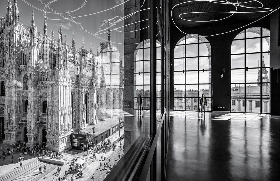 A black and white photo of the interior of a modern building next to a cathedral, with a woman reflected in glass