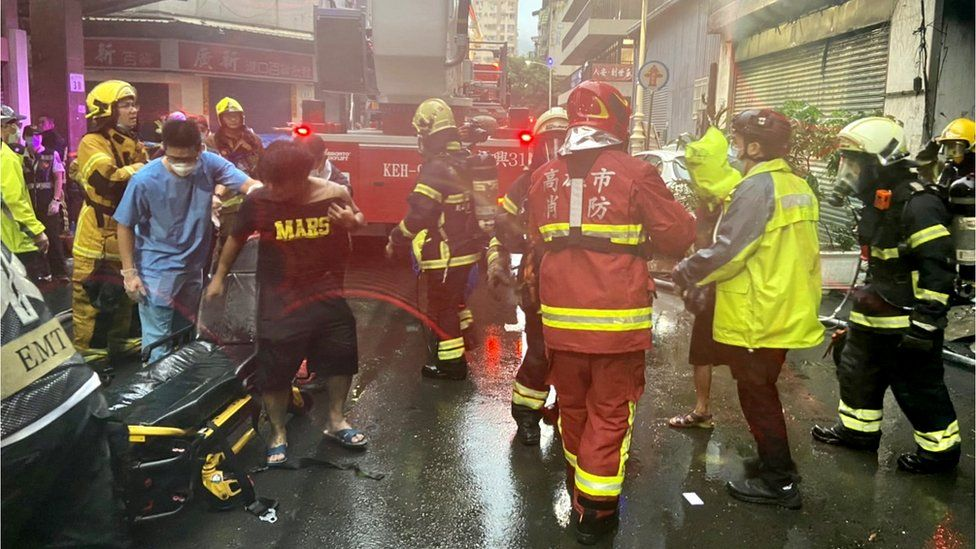 Rescuers assisting survivors after a fire on a commercial and residential building in Kaohsiung city, southern Taiwan, 14 October 2021
