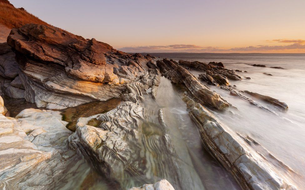 Waves lap over rocks as the sun rises at Bloody Bridge, near Newcastle in County Down