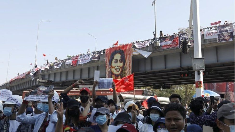 Demonstrators hold placards and shout slogans during a protest against the military coup at the Hledan junction in Yangon, Myanmar, 10 February 2021.