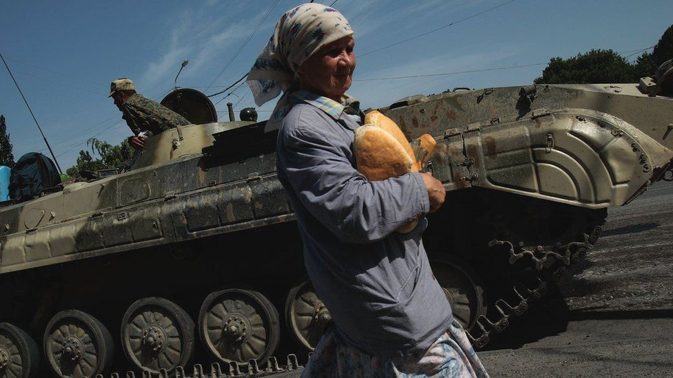 A Georgian woman carries humanitarian relief bread past a Russian checkpoint on 17 August 2008 in Gori, Georgia
