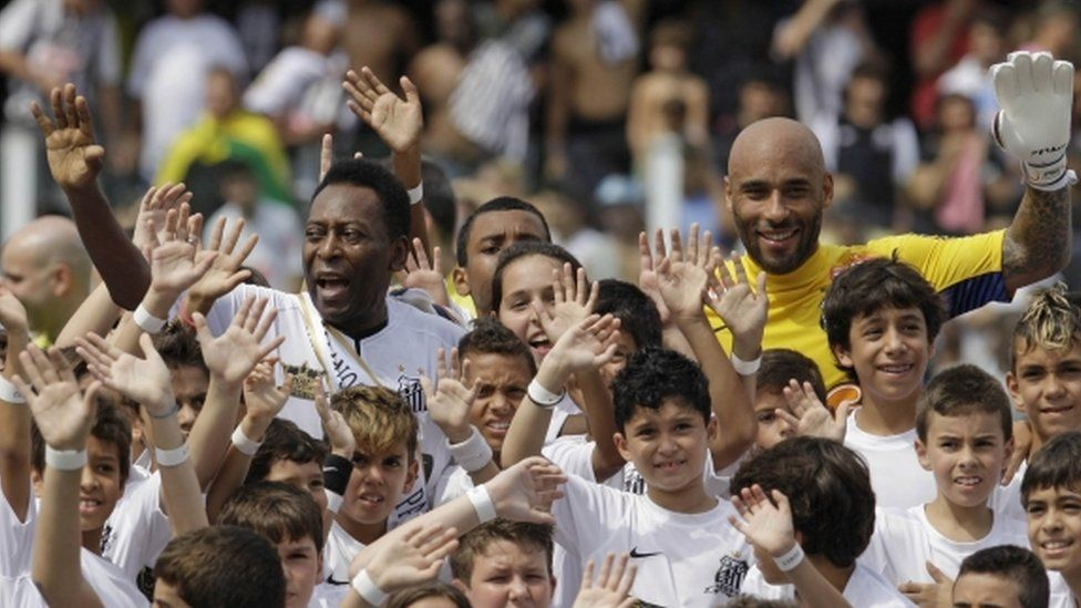 Pele (left) and Edinho (in yellow, right) during an event at Santos Football Club in April 2012