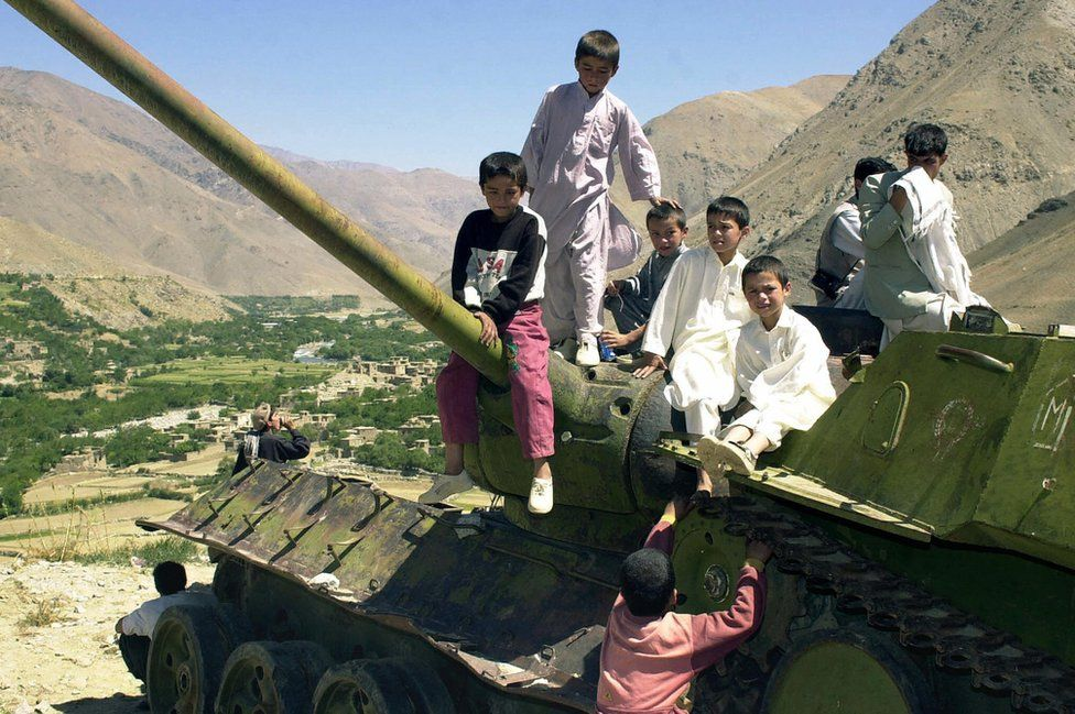 Afghan children play on the turret of an abandoned Soviet tank in the Panjshir valley , 2003