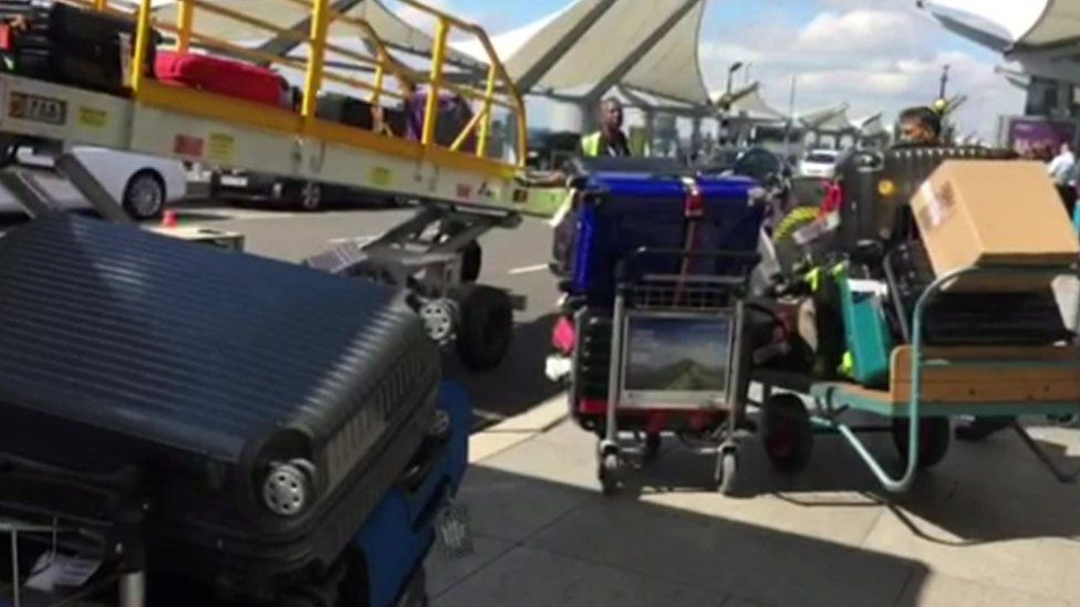 baggage handlers load luggage onto a plane