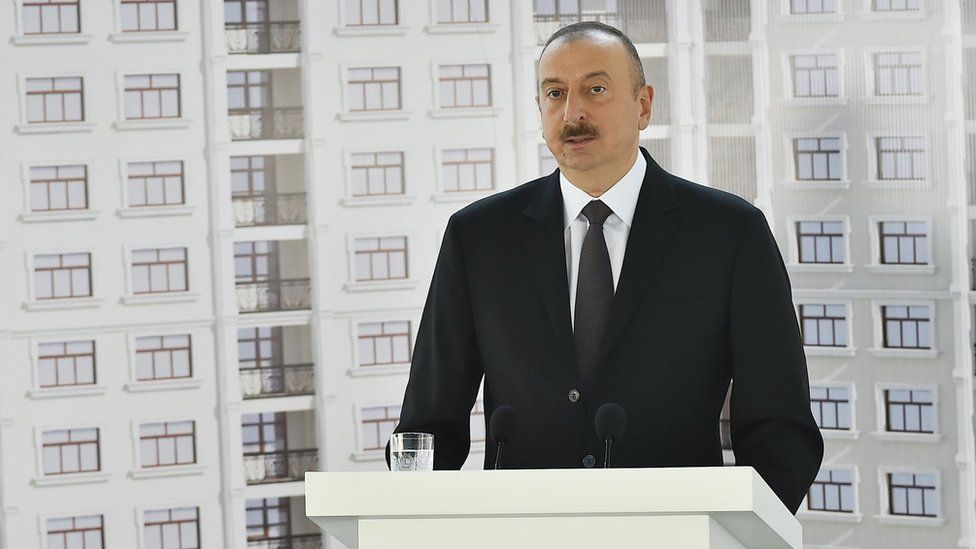 President Ilham Aliyev giving a speech in front of a picture of the flats