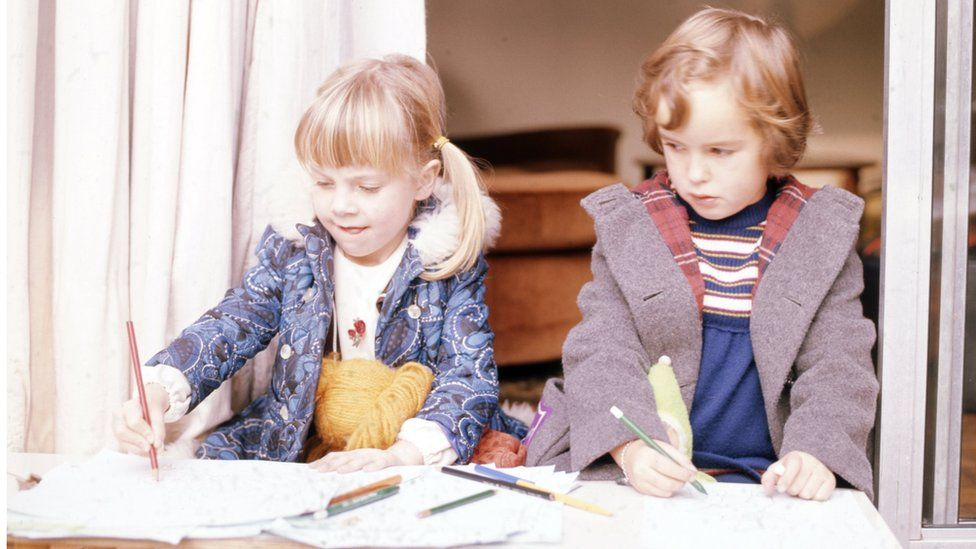 Two children sit next to each other, drawing with colouring pencils. The image is from the 1970s.