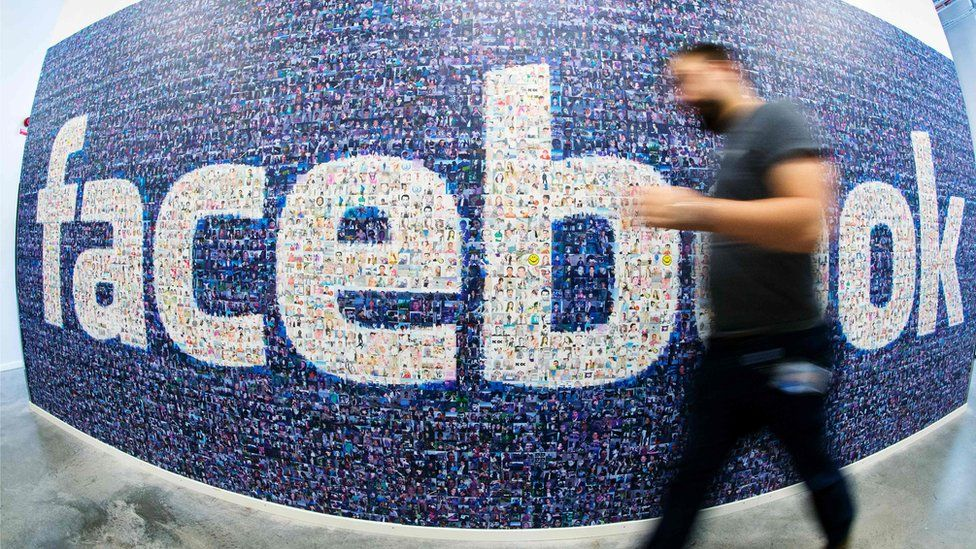 Man walking in front of a mural of Facebook users