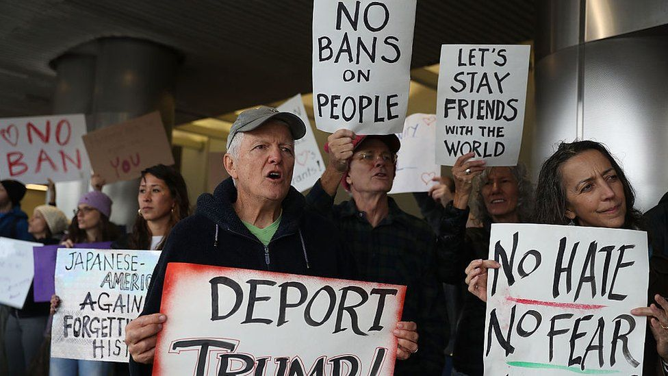 Protesters stand together at the Miami International Airpor