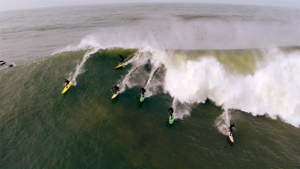 Several surfers riding a really impressive wave