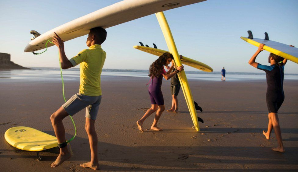Children balance boards on their heads as they walk to the shore's edge.