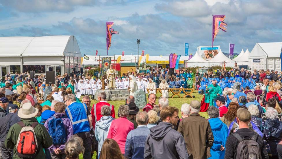 Gwerth straffaglu å'r mwd. beth bynnag, i weld seremoni drawiadol Cylch yr Orsedd. //It was worth wading through the mud to get to the colourful and dramatic Gorsedd of the Bards ceremony - one of the highlights of the National Eisteddfod.