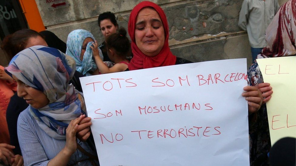Mother of Aallaa brothers holds a sign next to Hafida Oukabir (sister of suspect Moussa Oukabir) during a Muslim community rally in Ripoll to denounce terrorism