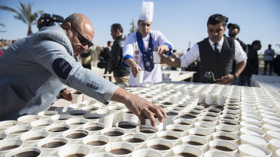 "Helpers arrange cups with black coffee and milk coffee to create a mosaic depicting the ancient Egyptian pharaoh Tutankhamun""s death mask outside the Grand Egyptian Museum (GEM), in Giza, Greater Cairo, Egypt, 28 December 2019. Media reports state that Guinness World Records organized the event to celebrate Egypt for ""breaking the world record with a picture of King Tutankhamun""s mask"" by using a total of 7,260 cups of coffee. The mosaic was meant as a ""symbol of love and greeting"" according to an Egyptian Ministry of Tourism and Antiques statement. The museum is scheduled to present its full Tutankhamun collection by the end of 2020."