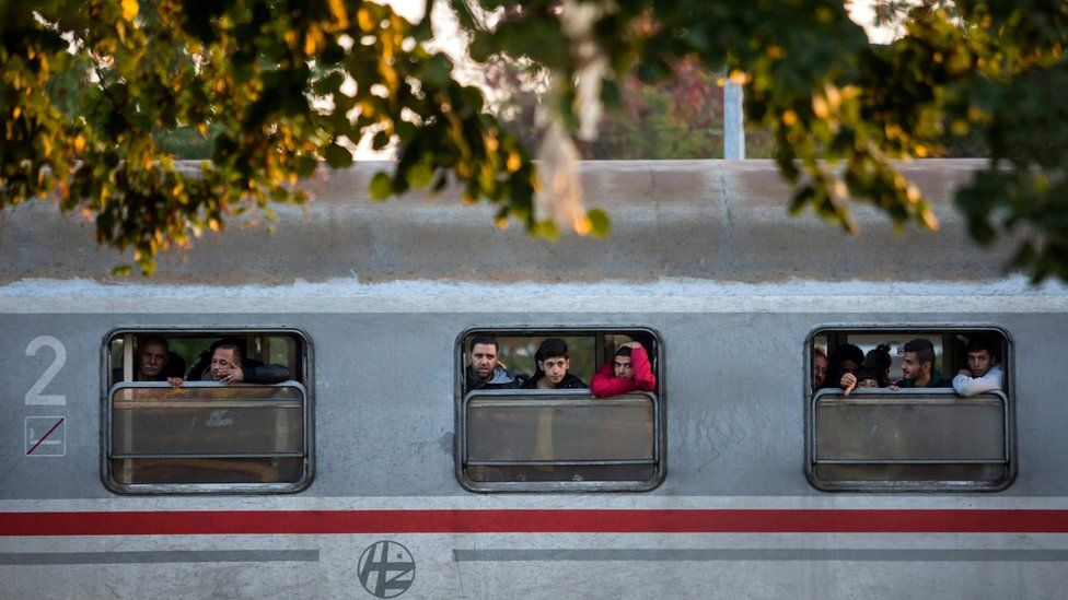 Migrants look from the windows of a train at the railway station in Cakovec, Northern Croatia, Saturday, Oct. 17, 2015.