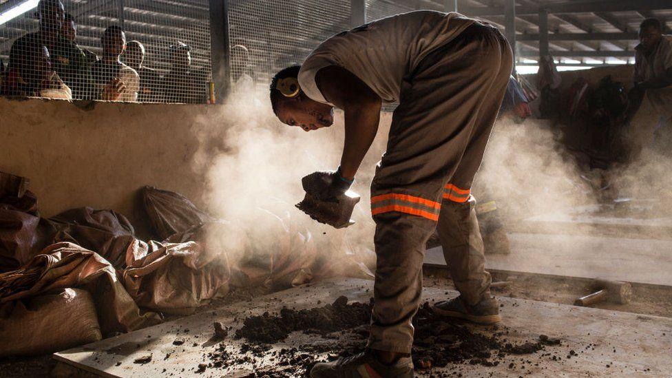 A miner crushes cobalt, Kolwezi, DR Congo