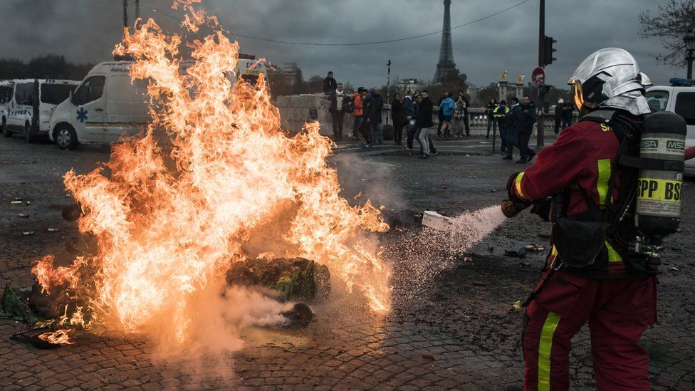 """Firefighters extinguish a fire lit on the street by ambulance drivers on Place de la Concorde during a national ambulance drivers"""" protest, in Paris, France, 03 December 2018"""