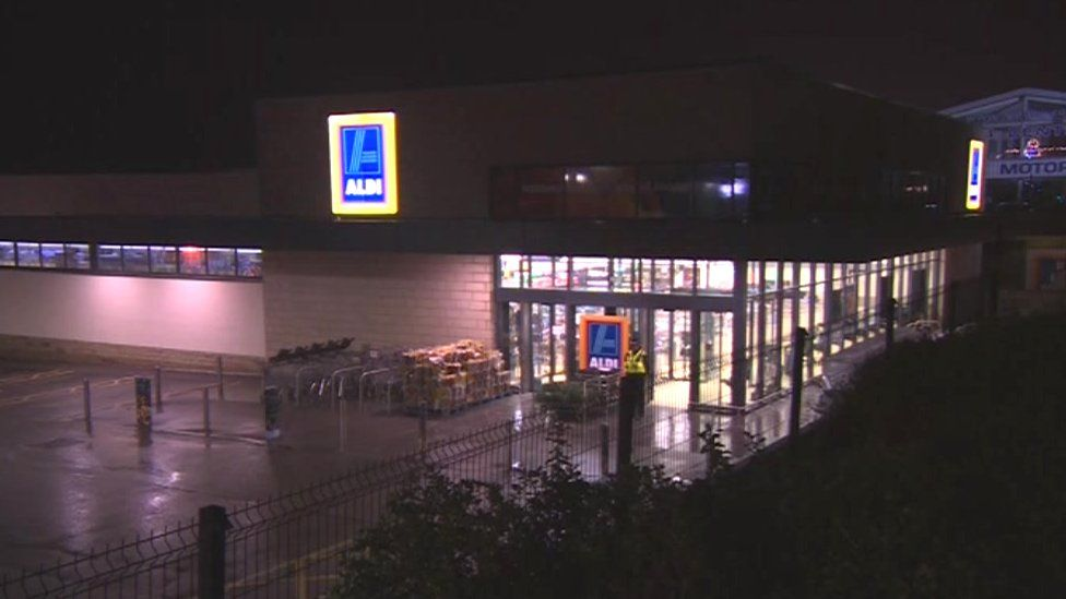 A wider shot of the Aldi store, at night