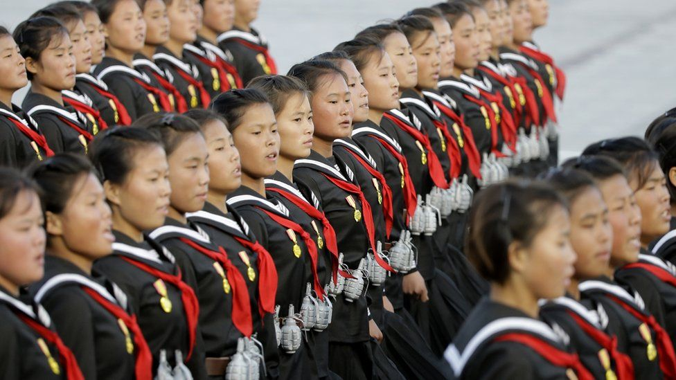 Schoolgirls wearing fake grenades during the military parade for the 70th anniversary of the founding Workers' Party, Pyongyang, North Korea - Saturday 10 October 2015