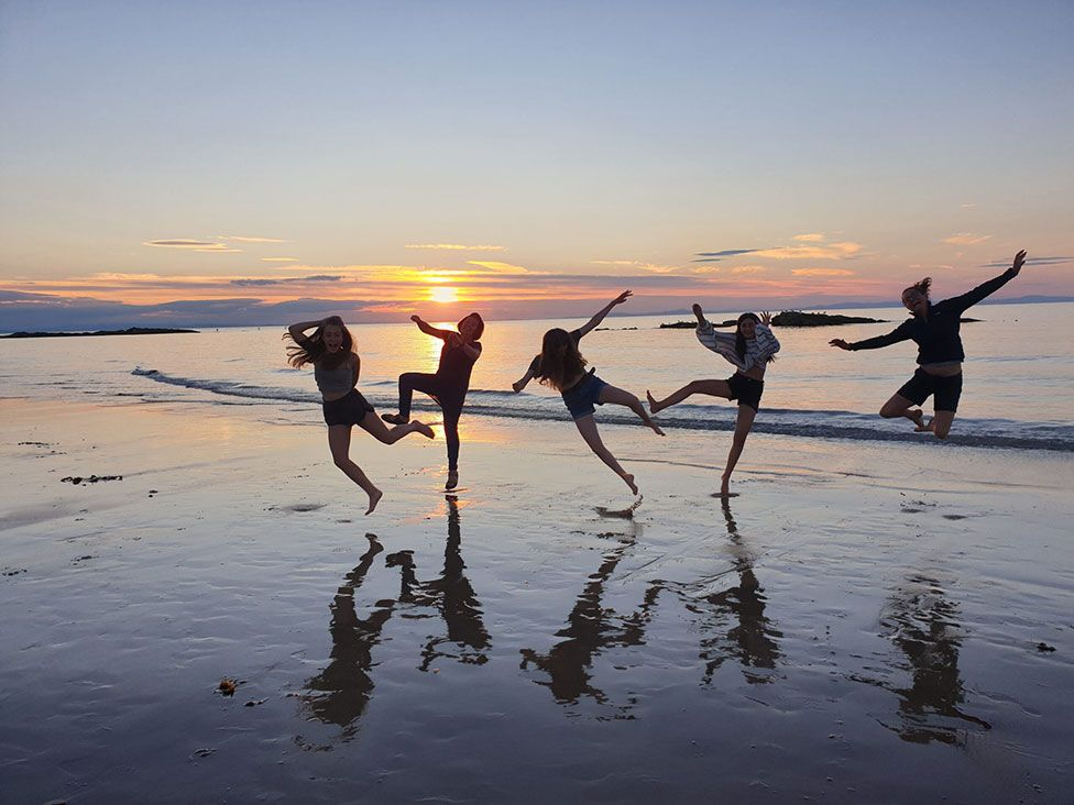 A group of people dance and jump on a beach as the sun sets