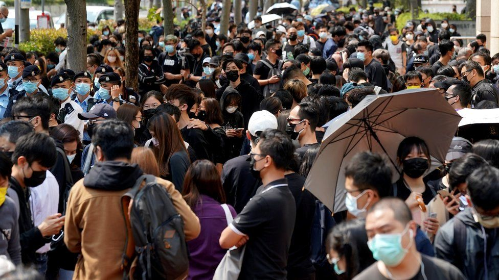 Supporters of pro-democracy activists gather outside West Kowloon Magistrates' Courts for a hearing over charges related to national security, in Hong Kong, 1 March 2021