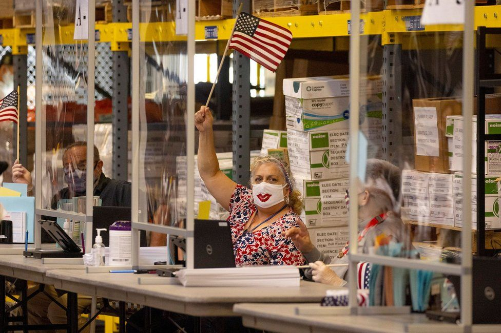 Poll workers wave US flags