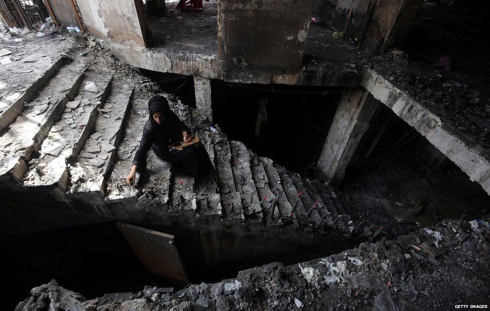 A woman sits in the rubble of a building after a bomb in Iraq claims nearly 300 lives