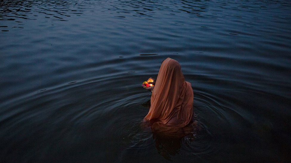 An Indian women offers early-morning prayers or a 'puja' at a ghat early in the morning on the banks of the Betawa River in Orchha in the state of Madhya Pradesh on July 5, 2015