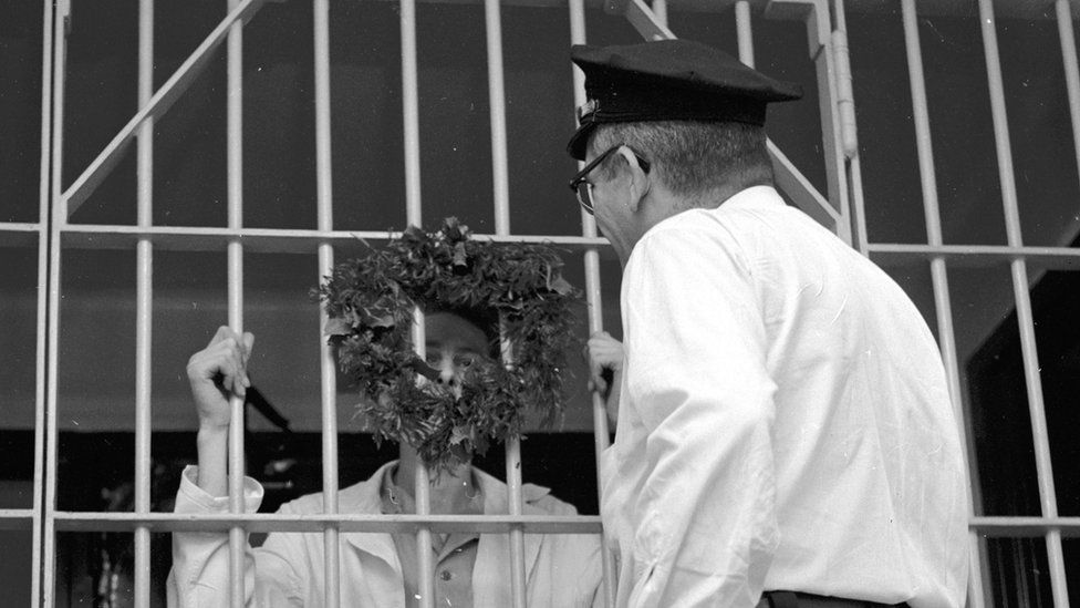 An inmate looking at his officer through a wreath attached to his prison cell bars