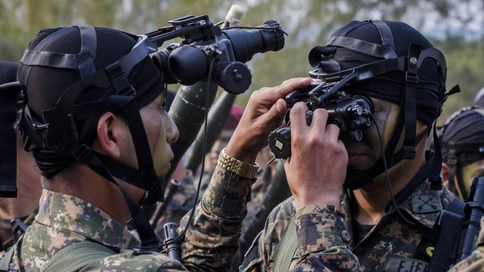 El Salvador army special forces try on their night vision goggles during a presentation to the press as part of a new stepped-up phase in the government's fight against gangs in San Salvador, El Salvador, Wednesday, April, 20, 2016.