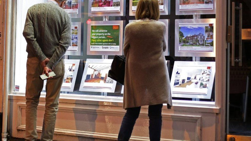 Couple looking in estate agent window