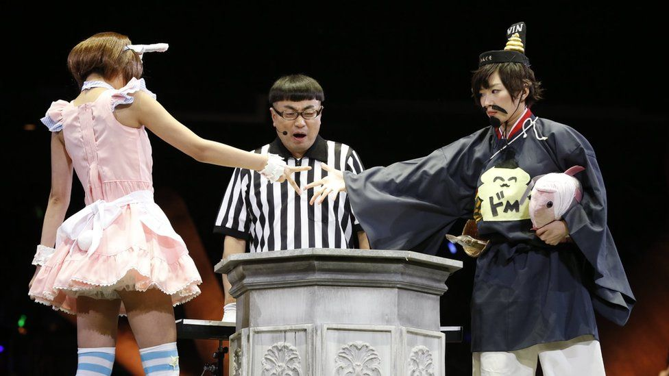 "Two women compete in the contest in 2014, with the woman on the left, in a pink dress, throwing ""scissors"", to defeat the woman on the right, wearing a fake moustache and dressed in a bizarre re-imagining of traditional Japanese clothing."
