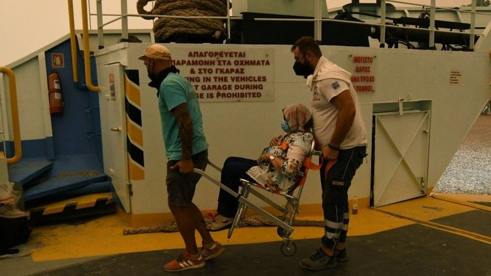 Locals carry a woman on board a ferry at the port of the village of Pefki