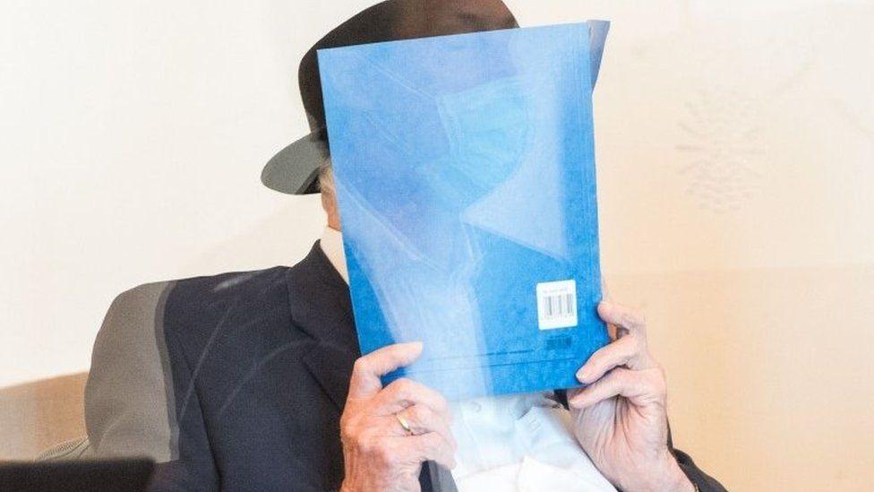 Bruno Dey hält sich am 23. Juli 2020 vor Gericht eine Mappe vors Gesicht